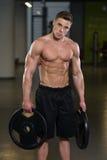 Подходящий человек держа весы в руке Стоковые Фотографии RF