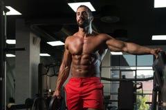 Подходящий человек держа весы в руке Стоковое Фото