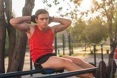 Подходящий человек делать сидит поднимает на станции фитнеса параллельных брусьев внешней стоковое изображение