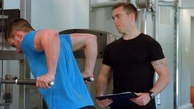 Подходящий человек делая тягу поднимает с тренером акции видеоматериалы