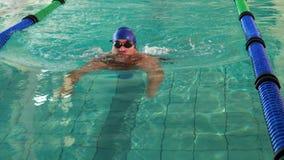 Подходящий человек делая ход груди и усмехаясь на камере в бассейне сток-видео