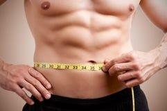 Подходящий человек измеряя его талию Стоковая Фотография RF