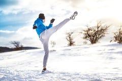 Подходящий человек практикуя пинок снял внешнее в снеге Тренировка игрока фитнеса Стоковая Фотография RF