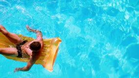 Подходящий человек сидя на lilo в бассейне сток-видео