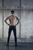 Подходящий sportive мышечный человек стоит назад к камере стоковые изображения rf