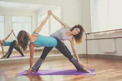 2 подходящих девушки протягивают ноги и заднюю часть совместно Стоковые Фотографии RF