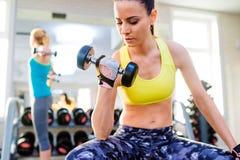 2 подходящих женщины в спортзале разрабатывая с весами Стоковое Изображение RF