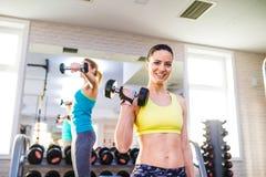 2 подходящих женщины в спортзале разрабатывая с весами Стоковые Фотографии RF
