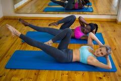 2 подходящих женщины делая протягивающ тренировку на циновке Стоковые Изображения