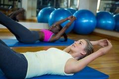 2 подходящих женщины делая протягивающ тренировку на циновке Стоковое фото RF