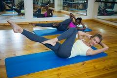 2 подходящих женщины делая протягивающ тренировку на циновке Стоковые Фотографии RF