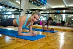 2 подходящих женщины делая протягивающ тренировку на циновке Стоковое Изображение RF