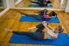2 подходящих женщины делая протягивающ тренировку на циновке Стоковые Изображения RF