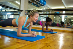 2 подходящих женщины делая протягивающ тренировку на циновке Стоковая Фотография RF
