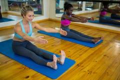 2 подходящих женщины делая протягивающ тренировку на циновке Стоковые Фото