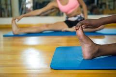 2 подходящих женщины делая протягивающ тренировку на циновке Стоковое Фото