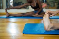 2 подходящих женщины делая протягивающ тренировку на циновке Стоковое Изображение