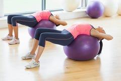2 подходящих женщины протягивая на шариках фитнеса в спортзале Стоковое Изображение