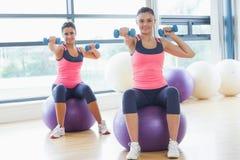 2 подходящих женщины работая с гантелями на шариках фитнеса Стоковая Фотография RF