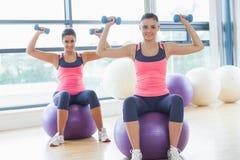 2 подходящих женщины работая с гантелями на шариках фитнеса Стоковые Фото