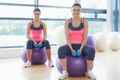 2 подходящих женщины с гантелями на шариках фитнеса в спортзале Стоковые Изображения