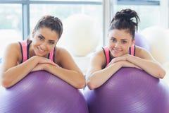 2 подходящих женщины с шариками тренировки на спортзале Стоковое Фото