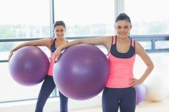 2 подходящих молодой женщины держа шарики тренировки на спортзале Стоковая Фотография