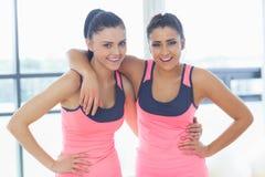 2 подходящих молодой женщины усмехаясь в яркой комнате тренировки Стоковые Изображения