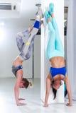 2 подходящих молодых кавказских девушки нося sportswear выполняя handstand против стены внутри помещения Стоковая Фотография
