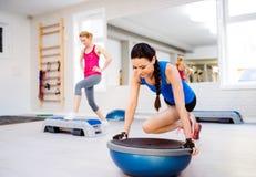 2 подходящих привлекательных женщины в спортзале делая различные тренировки Стоковая Фотография RF