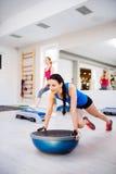 2 подходящих привлекательных женщины в спортзале делая различные тренировки Стоковое Изображение RF