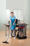 Пол чистки работника с пылесосом стоковое фото rf