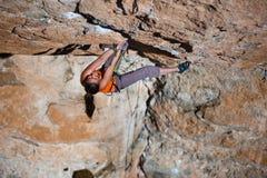 Подъемы альпиниста девушки на утесе Стоковая Фотография