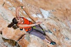 Подъемы альпиниста девушки на утесе Стоковое фото RF