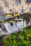 Подъемы альпиниста девушки на утесе Стоковые Фотографии RF