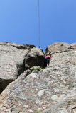 Подъемы альпиниста утеса девушки на утесе Стоковое Изображение