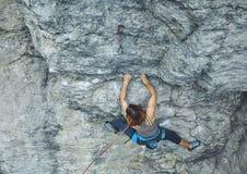 Подъемы альпиниста утеса женщины на скале Стоковые Изображения RF
