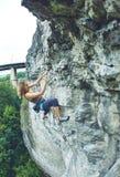 Подъемы альпиниста утеса женщины на скале Стоковые Фото