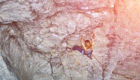Подъемы альпиниста утеса женщины на скале Стоковая Фотография