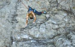 Подъемы альпиниста утеса женщины на скале Стоковые Изображения