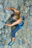 Подъемы альпиниста утеса женщины на скале Стоковое Изображение RF