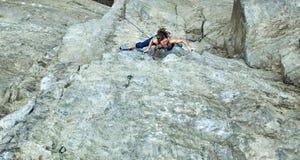 Подъемы альпиниста утеса женщины на скале Стоковая Фотография RF