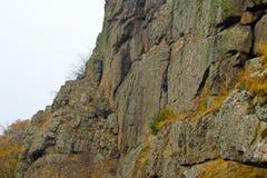 Подъемы альпиниста утеса мальчика на утесе Стоковые Фото
