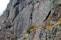 Подъемы альпиниста утеса мальчика на утесе Стоковые Изображения