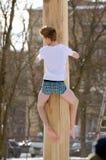 Подъемы человека над скользким деревом Стоковые Изображения