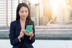 Польза бизнес-леди мобильного телефона в городе Стоковые Изображения RF