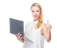 Польза женщины компьютер-книжки и большого пальца руки вверх Стоковые Фото