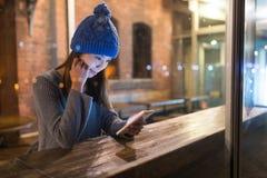 Польза женщины мобильного телефона внутри кафа на ноче стоковые изображения rf