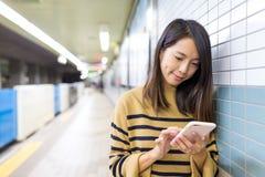 Польза женщины мобильного телефона на метро токио Стоковое Изображение