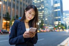 Польза коммерсантки мобильного телефона в городе токио Стоковое фото RF